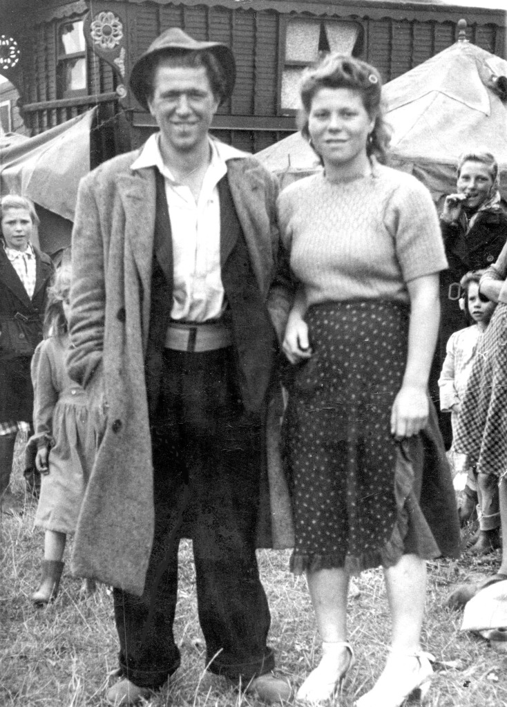 A black and white photo of a Traveller couple, dressed smartly and smiling